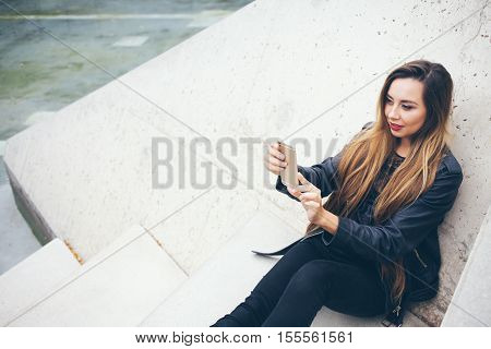 Beautuful smiles young teenage girl is sitting on the concrete steps and doing selfie photo. Student in alternative style clothes - black leather jacket and big boots. Copy-space area for your advertisement text or design