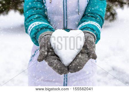 Snow heart in woman's heand. Winter romantic concept.