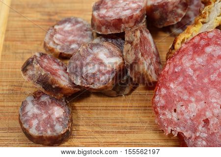 Close Up Of Different Meat Products (sausages, Salami, Breaded Chicken Breast) Arranged On A Wood Tr