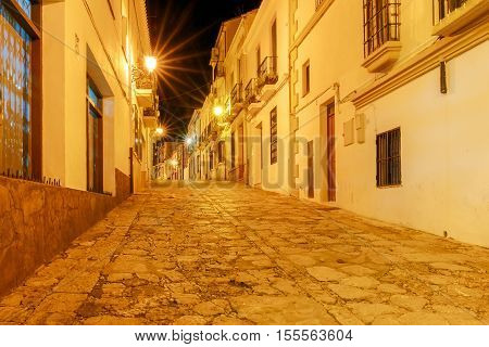 Traditional narrow village street with glowing lanterns in Ronda. Spain. Andalusia.