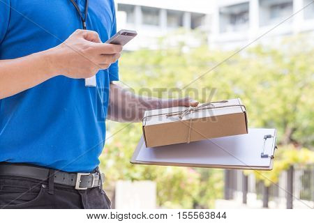 Delivery man holding a parcel box and calling contact to customer