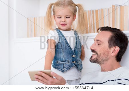 Something interesting. Nice positive delighted daughter and father looking at the screen of a cell phone and smiling while enjoying themselves