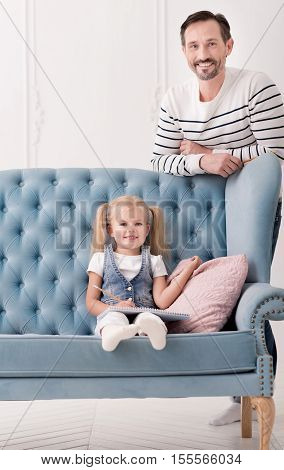 Future artist. Cute positive sweet girl sitting near the cushion on the sofa and smiling while drawing in her sketchbook