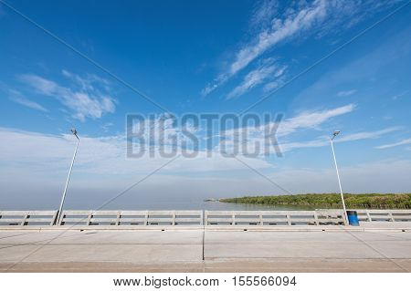 Clean beach bridge and footpath with two electric light poles and blue bin. Background is blue sky with slightly cloud.