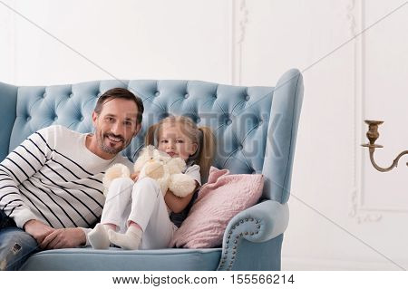 Homely atmosphere. Nice sweet blonde girl having ponytails and holding her teddy bear while sitting on the couch