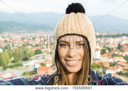 Selfie of young woman in knitted beige modern beanie hat. Closeup self portrait of beautiful blonde teenage girl, town urban area in the background. Natural light, mild retouch.