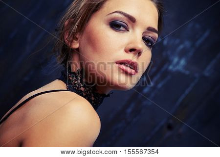 Extreme close-up of attractive woman face who is posing at the camera. Sensual glamour portrait of beautiful woman model lady with fresh smoky makeup with beige lips color and clean healthy skin face