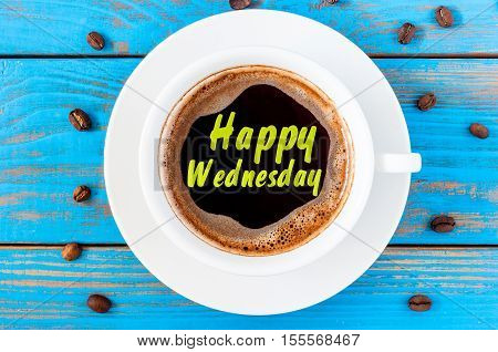 Happy Wednesday on top view coffee cup at blue wooden background with beans.