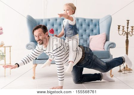 Playing the horse. Good looking positive brunette man being on all fours and holding his daughter while playing the horse
