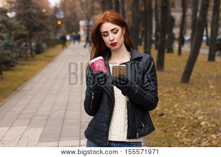Portrait Of Girl With A Cup Of Hot Coffee And With Mobile Phone. Girl Walking Through A Street And T