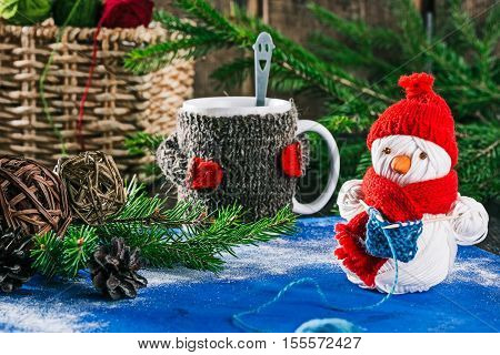 Handmade yarn snowman holding knitting on the background of christmas decorations and mug of hot drink