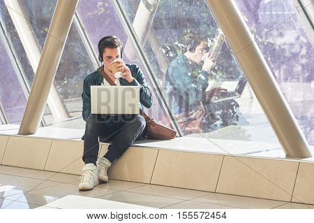 Young Male Entrepeneur Student Waiting Working On Laptop In Sunny Corridor