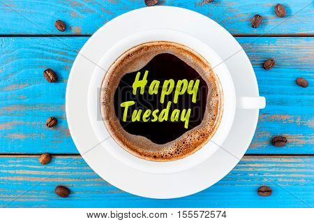 Happy Tuesday inspiration wish on top view cup of coffee at blue wooden background.