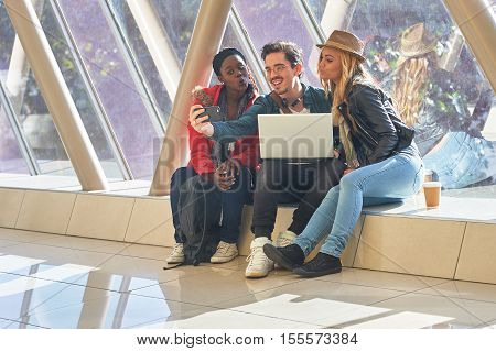 Mixed Race Group Of Students Entrepeneurs Taking Selfies Around A Laptop