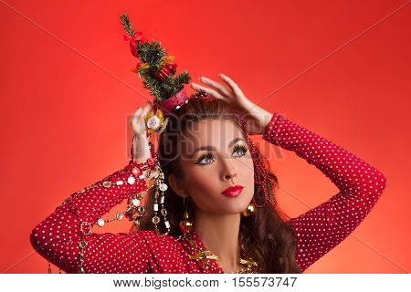 New Year's and Christmas efforts and preparations.Sad Girl with New Year tree instead of santa hat on head thinks about winter holidays celebration. Woman arranging decorations of Xmas tree. Creative fun studio photo.