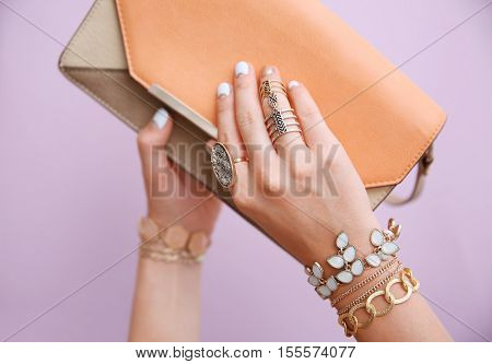 Female hands with jewelry and clutch bag on color background
