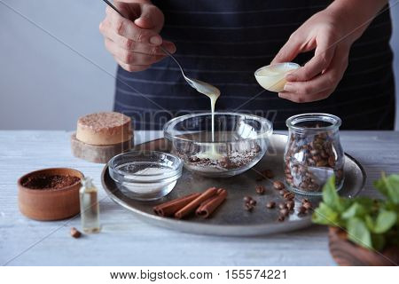 Woman making coffee body scrub on wooden table