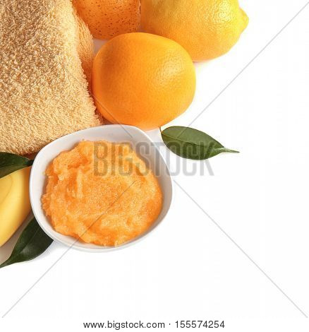 Small bowl with scrub, towel and citrus fruits on white background