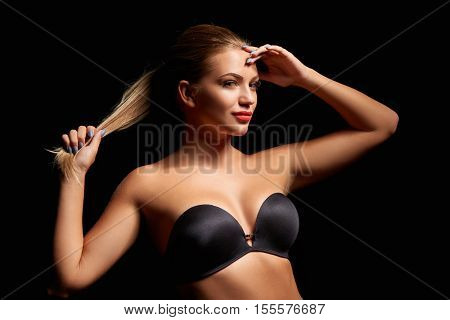 Fashion portrait of a young woman in black bra holding her hair tied in ponytail over dark background