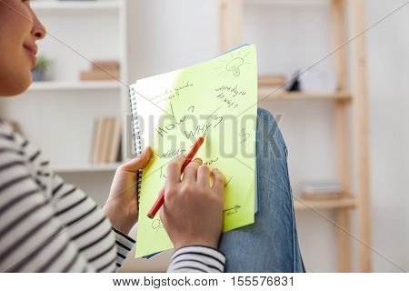 What I should do to make my life better. Cheerful young woman is writing her ideas on paper. She is sitting and smiling