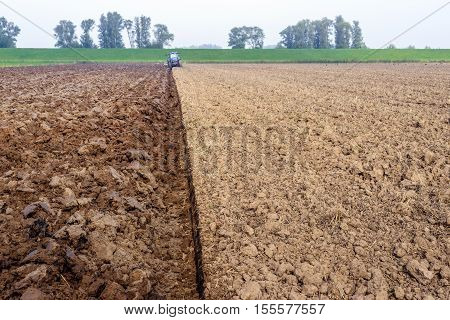 Farmer in a blue tractor with attached plow prepares the farmland in the Dutch polder before the start of the new growing season.