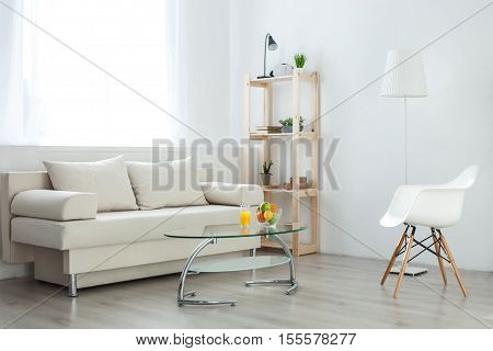 Modern comfortable furniture and homely atmosphere in living room. Fruits and juice on small table near white sofa