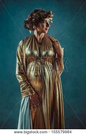 Pregnant Woman In Golden Toga And Wreath Posing Like A Greece Fertility Goddess