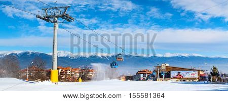 Bansko, Bulgaria - February 19, 2015: Bansko ski resort panorama with cable car ski lift cabin. Snow mountain peaks and houses