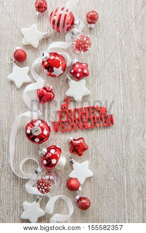 Various christmas baubles and glittery xmas decorations Frohe Weihnachten translates to Merry Christmas