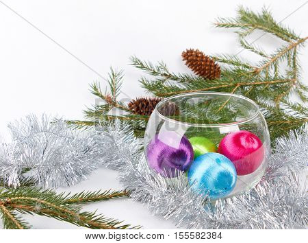 Colored christmas balls in a glass vase among fluffy silver tinsel on background of fir-tree brunches