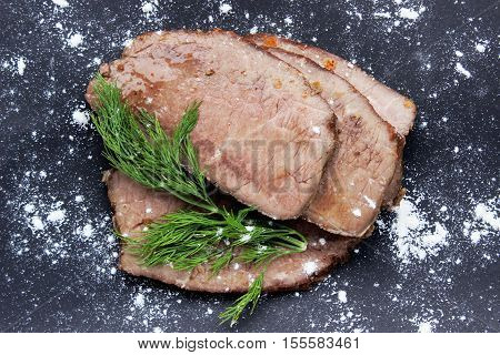 Sliced beef with balsamic and dill on a black background. View from above with copy space
