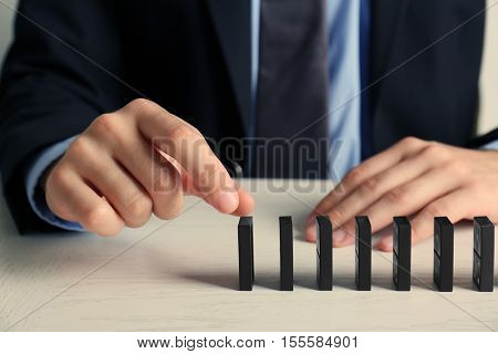 Businessman hand trying to toppling dominoes on table