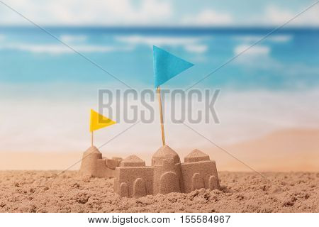 Sandcastles with flags close-up on a background of the sea.