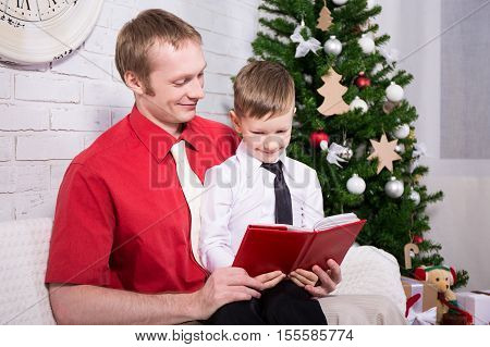 Young Father Reading Book To His Son In Front Of Christmas Tree