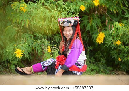 Beautiful asian young lady Lahu tribe sit in maxico flower field with smile and happy.