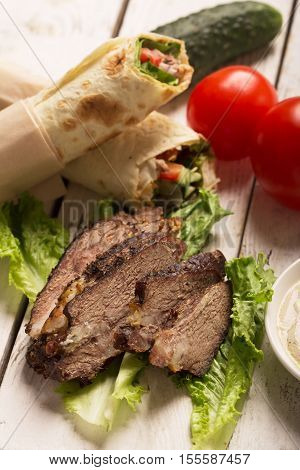 Doner kebab - fried beef meat with vegetables in tortilla