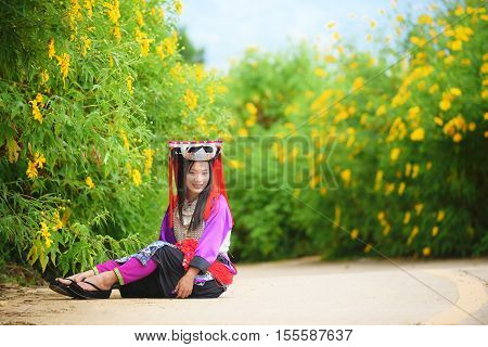 Beautiful asian young lady Lahu tribe in custom dress sit in maxico flower field with smile and happy.