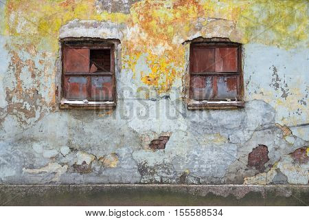 the broken windows on the old destroyed wall of the ancient house or brick building