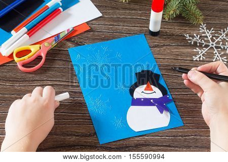 Child Paper Glued Details. The Child Makes A Greeting Card With A Snowman. Glue, Paper, Scissors On