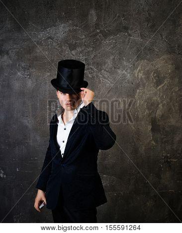 Illusionist man in cylinder hat on a dark background.