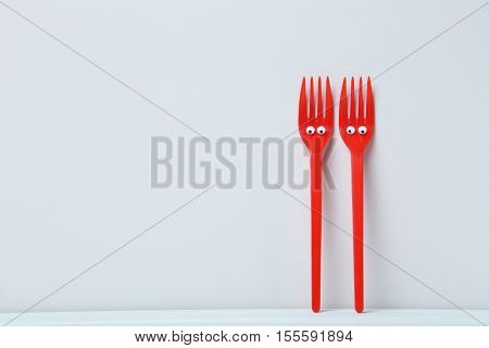Red Plastic Forks With Googly Eyes On A Grey Background