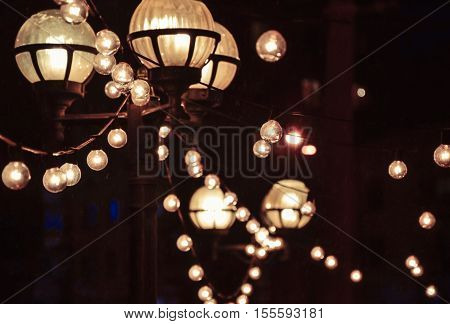 Glowing lanterns and light bulbs in dark at night on black background