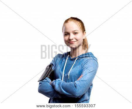 Teenage girl in blue sweatshirt, wearing phone armband, arms crossed. Beautiful young sportswoman, studio shot on white background, isolated.