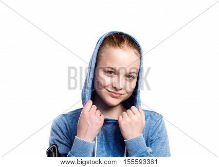 Teenage girl in blue sweatshirt, wearing phone armband, hood on head. Beautiful young sportswoman, studio shot on white background, isolated.