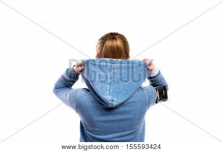 Teenage girl in blue sweatshirt, wearing phone armband, holding hood. Beautiful young sportswoman, studio shot on white background, isolated. Rear view.