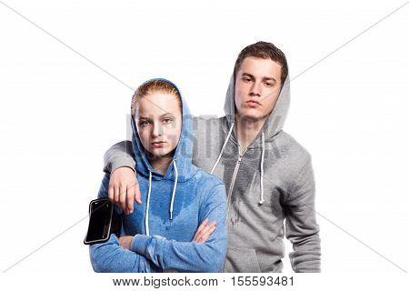 Teenage boy and girl in sweatshirts, wearing phone armband, hoods on heads. Studio shot on white background, isolated.
