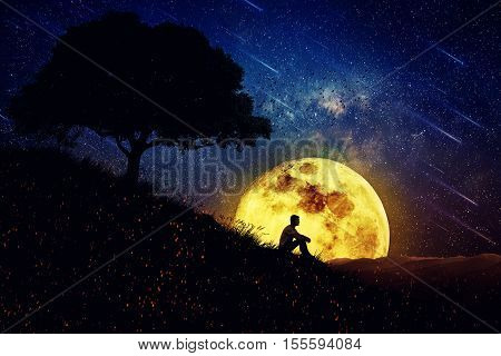 Boy sit alone on a hill in the center of nature over a full moon night background. Standing away from the crowd waiting for the healing power of the nature.