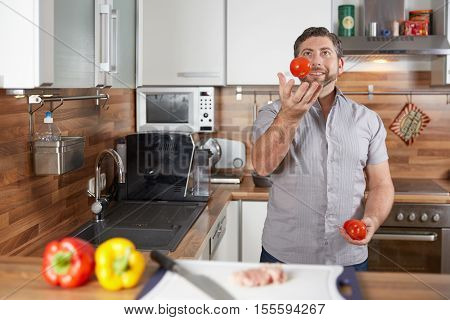 Man Juggling In The Kitchen With Tomatoes