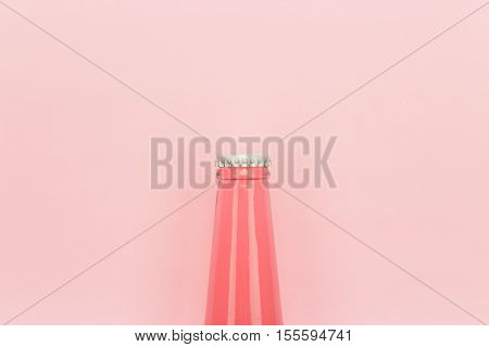 glass bottle of pinkish soda drink on pink background