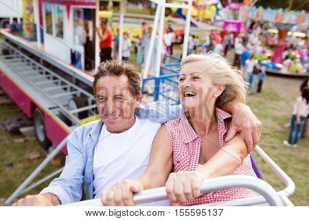 Senior couple having fun on a ride in amusement park. Summer vacation.